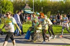Homme dans le fauteuil roulant couvert dans la poudre colorée Image stock