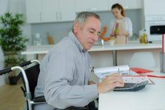 Homme dans le fauteuil roulant effectuant le travail de bureau à la maison images libres de droits