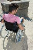 Homme dans le fauteuil roulant essayant de trouver la solution pour des ?tapes dehors photographie stock libre de droits