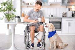 Homme dans le fauteuil roulant faisant cuire avec le chien de service Photographie stock libre de droits