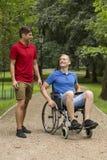 Homme dans le fauteuil roulant passant le temps avec l'ami Image libre de droits