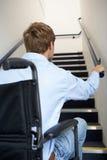 Homme dans le fauteuil roulant regardant vers le haut des escaliers Images stock
