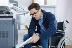 Homme dans le fauteuil roulant remplissant le magasin de photocopieur image stock