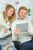 Homme dans le fauteuil roulant utilisant la tablette avec l'amie Photographie stock libre de droits