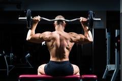 Homme dans le gymnase ou studio de forme physique sur le banc de poids Image libre de droits