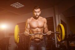 Homme dans le gymnase Type musculaire de bodybuilder faisant des exercices avec le barbell Personne intense Folâtre le fond Jeune photos libres de droits