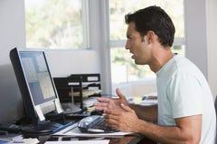 Homme dans le Home Office utilisant l'ordinateur Photo libre de droits