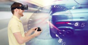 Homme dans le jeu de courses d'automobiles de casque et de réalité virtuelle Photos libres de droits