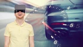 Homme dans le jeu de courses d'automobiles de casque et de réalité virtuelle Photo libre de droits