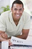 Homme dans le journal et le sourire du relevé de cuisine Images stock