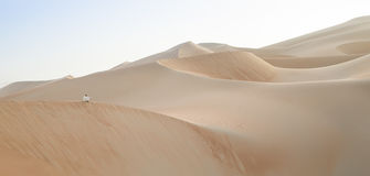 Homme dans le kandura dans un désert au lever de soleil Photos stock