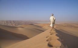 Homme dans le kandura dans un désert au lever de soleil Photo libre de droits