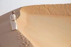 Homme dans le kandura dans un désert au lever de soleil Photos libres de droits