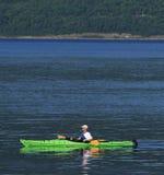 Homme dans le kayak de mer verte Photo stock