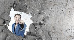 Homme dans le kimono cassant le mur Image libre de droits