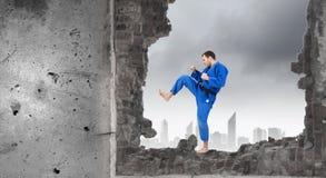 Homme dans le kimono cassant le mur Image stock
