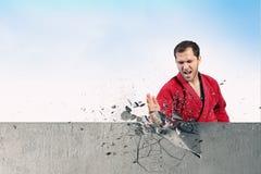 Homme dans le kimono cassant le mur Photographie stock libre de droits