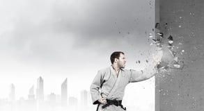 Homme dans le kimono cassant le mur Photo stock