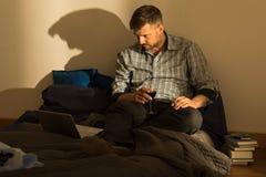 Homme dans le lit désordonné Photographie stock