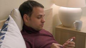 Homme dans le lit utilisant le smartphone dû à l'insomnie Image stock