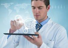 Homme dans le manteau de laboratoire avec le comprimé et interface blanche sur le fond bleu avec l'interface images libres de droits