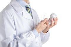 Homme dans le manteau médical tenant une ampoule de l'impression 3d et vraie Photographie stock