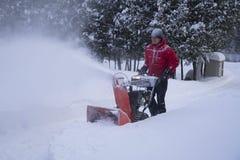 Homme dans le manteau rouge utilisant le lanceur de neige dans l'allée Photo libre de droits