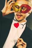 Homme dans le masque de carnaval avec le symbole d'amour de bâton de coeur Image stock