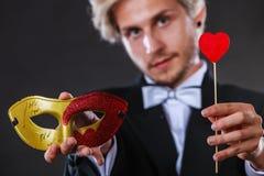 Homme dans le masque de carnaval avec le symbole d'amour de bâton de coeur Images stock