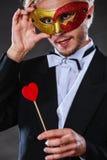Homme dans le masque de carnaval avec le symbole d'amour de bâton de coeur Image libre de droits