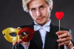 Homme dans le masque de carnaval avec le symbole d'amour de bâton de coeur Photo libre de droits