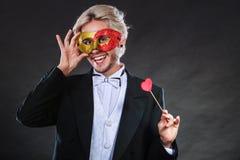 Homme dans le masque de carnaval avec le symbole d'amour de bâton de coeur Photo stock