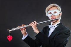 Homme dans le masque de carnaval jouant la cannelure Images stock