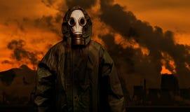 Homme dans le masque de gaz et le manteau de la protection chimique avec des usines d'industrie lourde photo libre de droits