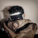 Homme dans le masque noir avec le regard insidieux Photo stock