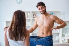 Homme dans le pantalon surdimensionné dans le concept de perte de poids avec des WI d'amie Photo stock