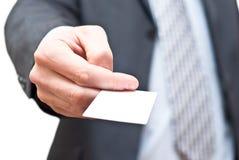 Homme dans le procès foncé donnant une carte de visite professionnelle de visite vide Image libre de droits