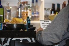 Homme dans le pull gris se reposant à la barre de tequila avec la cuvette de puces et de bouteilles de bokeh évidentes sur l'étag image stock