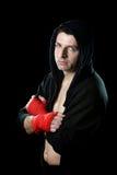 Homme dans le pullover de hoodie de boxe avec le capot sur la tête avec les poignets enveloppés de mains prêts à combattre Photo stock