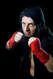 Homme dans le pullover de hoodie de boxe avec le capot sur la tête avec les poignets enveloppés de mains prêts pour le combat Photographie stock libre de droits