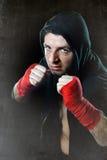 Homme dans le pullover de hoodie de boxe avec le capot sur la tête avec les poignets enveloppés de mains prêts pour le combat Photo libre de droits