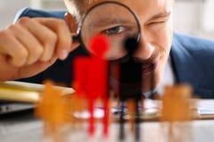 Homme dans le regard de costume par la loupe sur le plan rapproché de statuettes Photos libres de droits