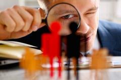 Homme dans le regard de costume par la loupe sur le plan rapproché de statuettes Photographie stock libre de droits