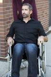Homme dans le regard extérieur de fauteuil roulant sûr Images stock