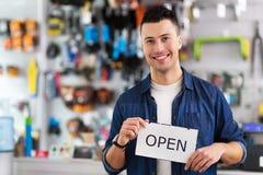 Homme dans le signe ouvert de participation de boutique de vélo Photos stock