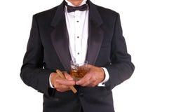 Homme dans le smoking avec la boisson et le cigare Photo stock