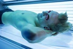 Homme dans le solarium appréciant prendre un bain de soleil sur le lit de bronzage Image stock