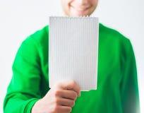 Homme dans le sourire de pull molletonné de verdure, main tenant la note en spirale vide Photo stock