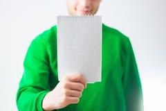 Homme dans le sourire de pull molletonné de verdure, main tenant la note en spirale vide Image stock