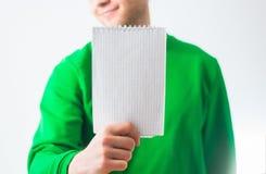 Homme dans le sourire de pull molletonné de verdure, main tenant la note en spirale vide Photos libres de droits